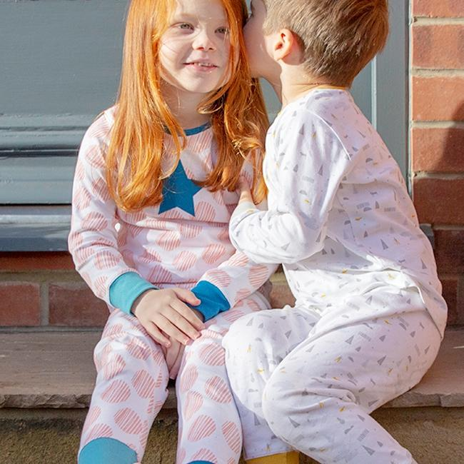Children wearing Lister & Bruce pyjamas sitting on a step whispering