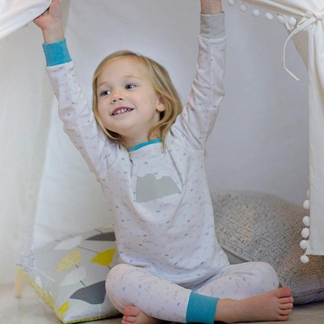 Little girl in soft mountain and polar bear pyjamas. Super soft organic cotton with pale greys and blues