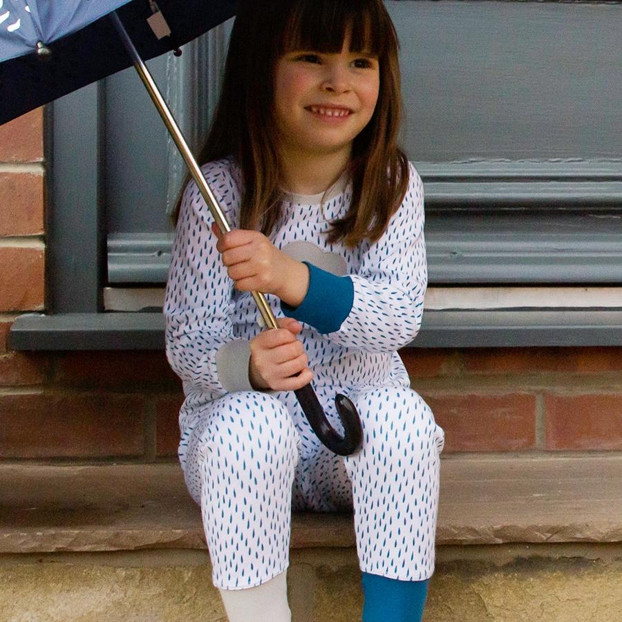 Little girl with umbrella on step in blue and grey unisex rain cloud pyjamas