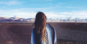 woman with long brown hair shown from back draped in blue, black, grey and white Mexican blanket, facing distant snowcapped mountains and blue sky