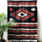 Mexican blanket with woven in geometric design with center diamond and stripes in black, rust, brown, and tan with white fringe shown hanging against white wall with palm plant at side