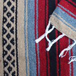 Close-up of blanket woven with alternating solid stripes in black, grey, burgundy and tan, and tan stripe with pattern of small black diamonds, edge of blanket has white fringe.