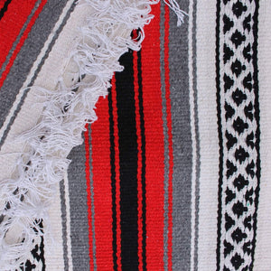 Close-up of blanket woven with alternating solid stripes in white, black, grey and chocolate brown, and white stripe with pattern of small black diamonds, edge of blanket has white fringe.