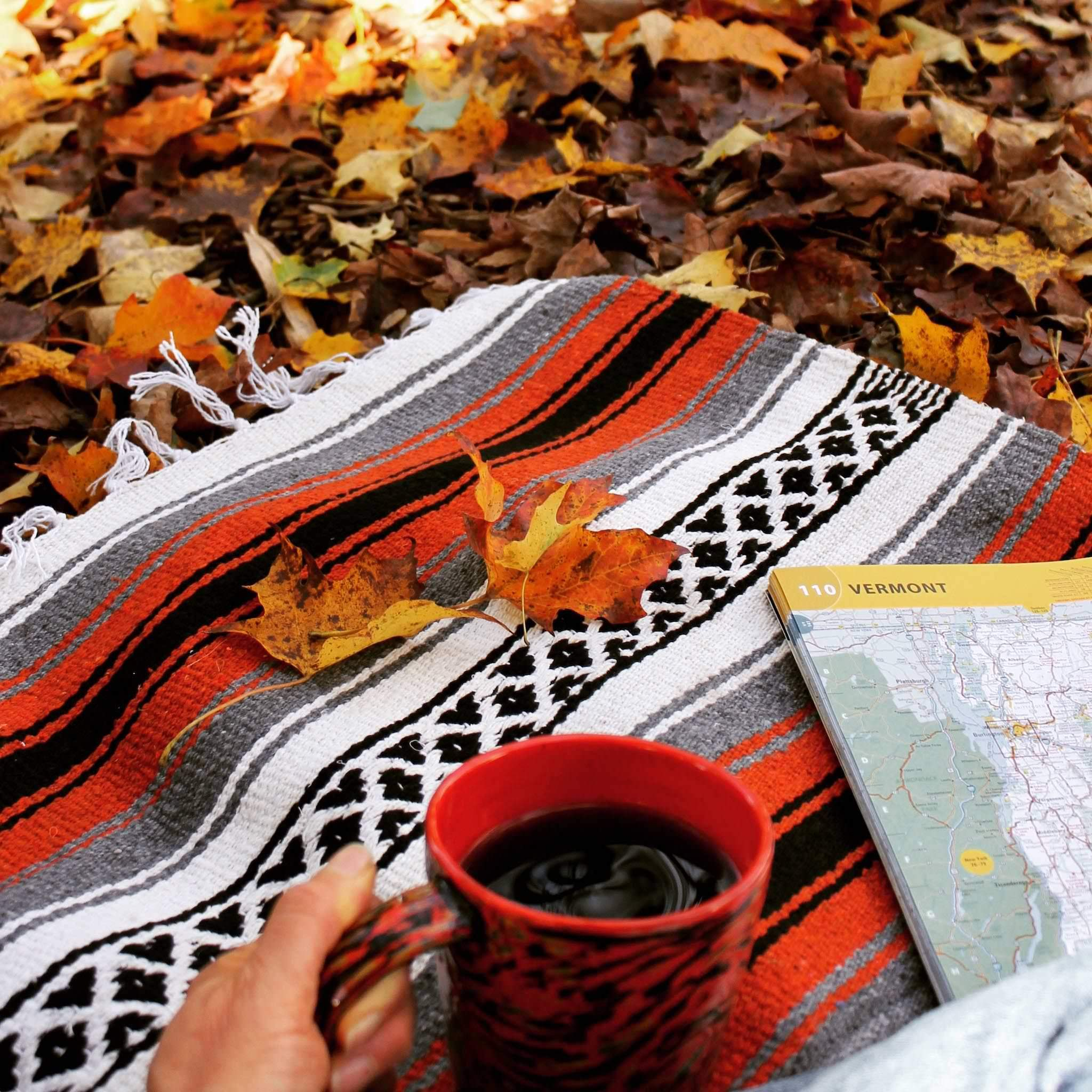 Corner of blanket woven with alternating solid stripes in white, black, grey and rusty orange, and white stripe with pattern of small black diamonds, and white fringed edge, lying on ground covered with yellow and brown fallen leaves, with hand holding an orange ceramic cup full of coffee and corner of map of Vermont resting on blanket.