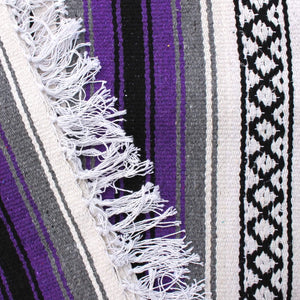 Close-up of blanket woven with alternating solid stripes in white, black, grey and bright purple, and white stripe with pattern of small black diamonds, edge of blanket has white fringe.