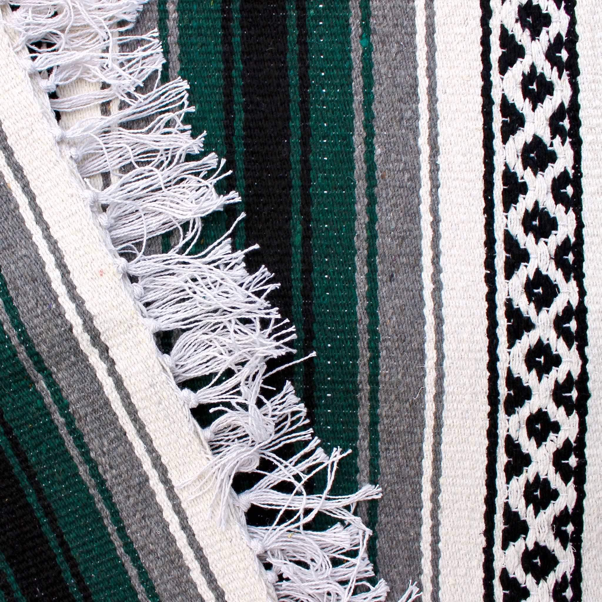 Close-up of blanket woven with alternating solid stripes in white, black, grey and hunter green, and white stripe with pattern of small black diamonds, edge of blanket has white fringe.