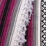 Close-up of blanket woven with alternating solid stripes in white, black, grey and deep raspberry pink, and white stripe with pattern of small black diamonds, edge of blanket has white fringe.