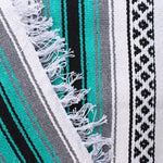 Close-up of blanket woven with alternating solid stripes in white, black, grey and bright teal, and white stripe with pattern of small black diamonds, edge of blanket has white fringe.