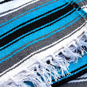 Close-up of blanket woven with alternating solid stripes in white, black, grey and bright turquoise, and white stripe with pattern of small black diamonds, edge of blanket has white fringe.