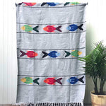 Woven blanket in light grey with pattern of three multicolored fish in four alternating stripes, with white fringed edge, shown hanging against white wall with potted palm plant at side.