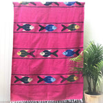 Woven blanket in hot pink with pattern of three multicolored fish in four alternating stripes, with white fringed edge, shown hanging against white wall with potted palm plant at side.