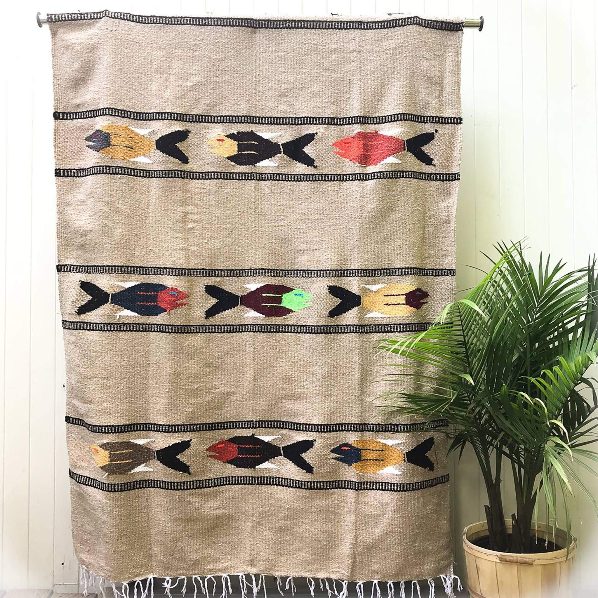 Woven blanket in natural tan with pattern of three multicolored fish in four alternating stripes, with white fringed edge, shown hanging against white wall with potted palm plant at side.