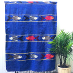 Woven blanket in royal blue with pattern of multicolored fish in four stripes, alternating with wide stripes of royal blue, with white fringed edge, shown hanging against white wall with potted palm plant at side.