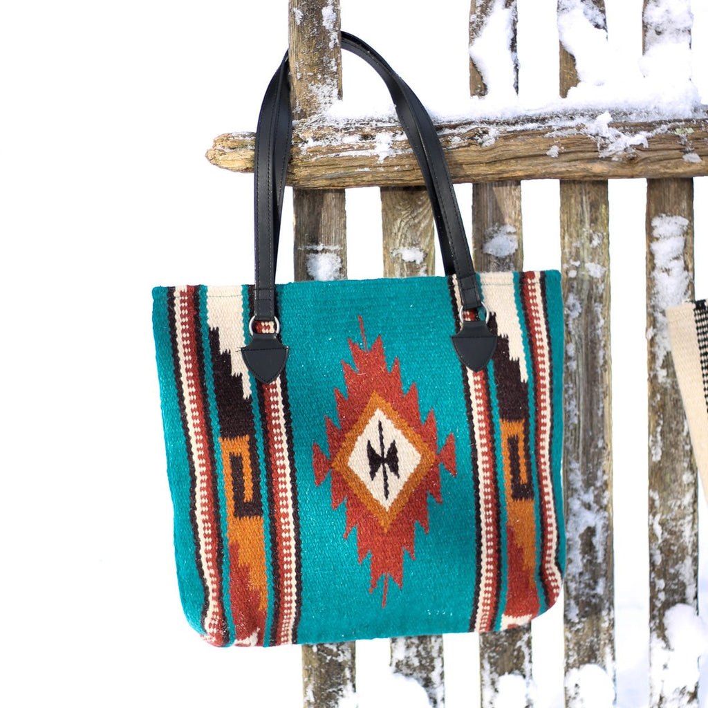 Handwoven wool handbag with center diamond design in turquoise and rust with black, cream and tan accents and black straps hanging from snow covered wood fence.