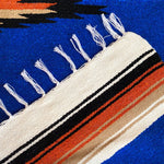 Mexican-style blanket in woven in cobalt blue with rust, tan, black and white stripes, center diamond design and white fringed edge.