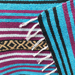 Close up of woven blanket with stripe design in turquoise, dark pink, white, tan and black, with folded corner showing white fringed edge.