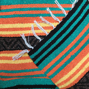 Close up of woven blanket with stripe design in orange, yellow, teal, brown and black, with folded corner showing white fringed edge.