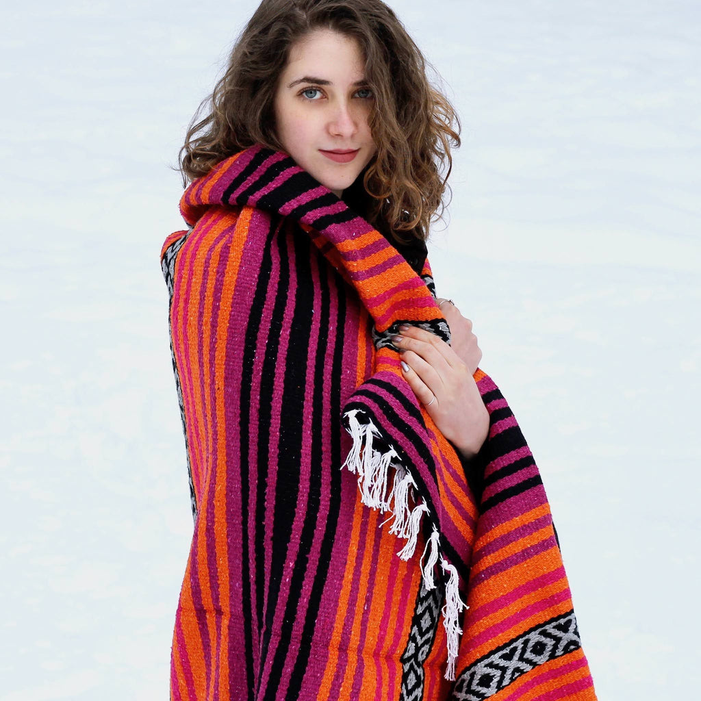 Young woman with brown hair, blue eyes, pale skin shown from waist up, looking into camera, hand on chest holding dark pink, orange, black striped blanket with white fringe draped around her shoulders