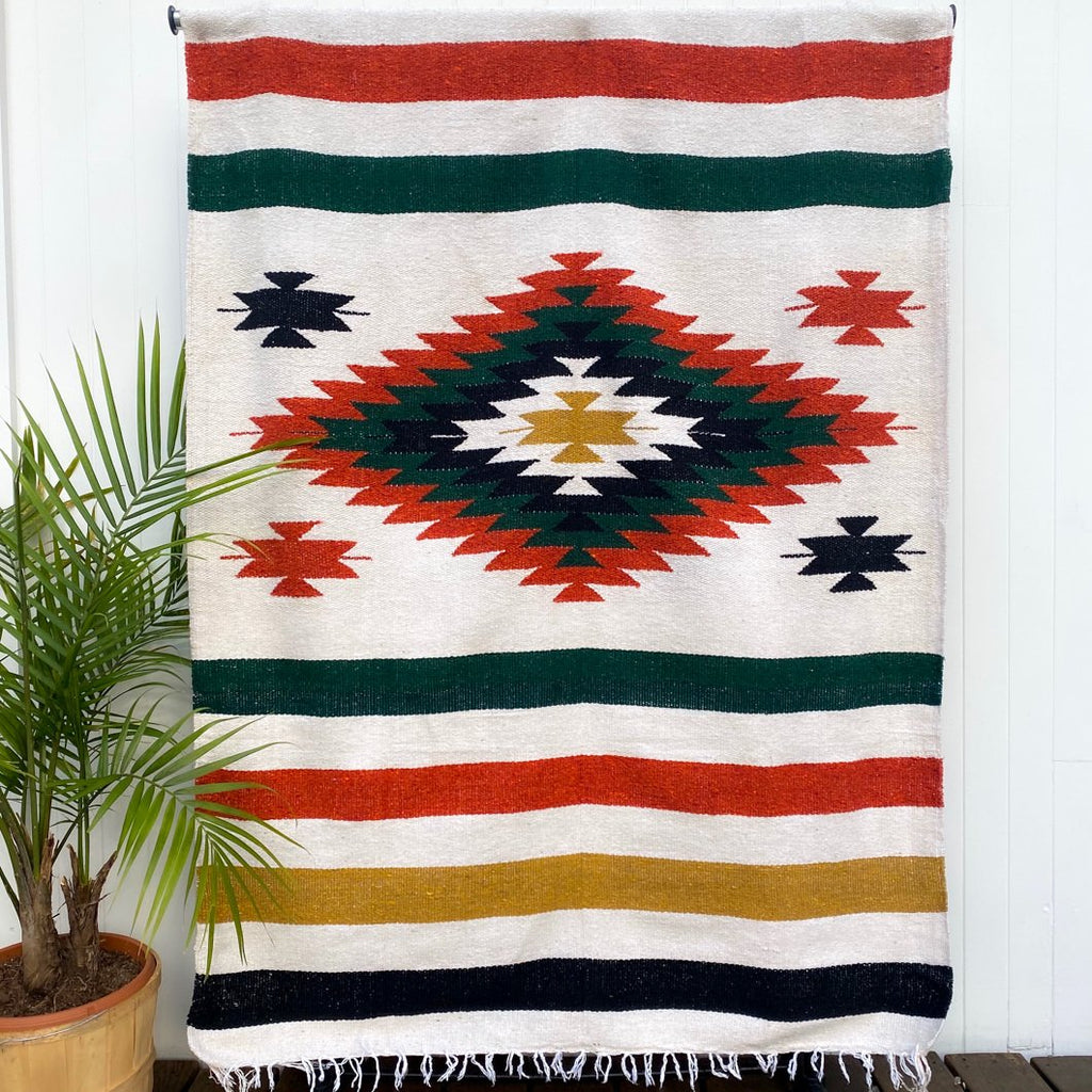Handwoven Mexican blanket with center diamond design in gold, green, rust and black on a natural background shown hanging on a white wall with potted palm plant at side