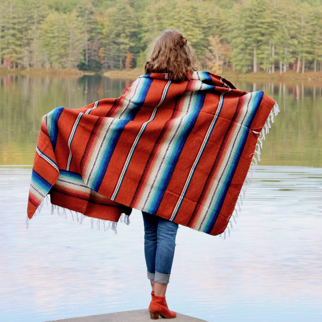 woman with light brown hair, wearing blue jeans and orange boots, seen from behind with arms outstretched and holding Rio Bravo blanket draped across her shoulders, showing blanket design of solid dark orange stripes alternating with multicolored stripes of blue, teal, red, black and white, standing against background of green trees reflected in water.