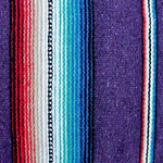 Close up of woven blanket showing wide deep purple stripe alternating with section of narrow stripes in blue, teal, white, black, tan and red.