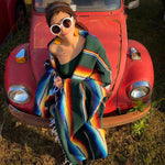 Woman draped in green and multi-color striped Mexican Southwest blanket standing in front of vintage VW Beetle