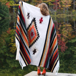 Woman with light brown hair shown from behind with San Miguel blanket draped around her shoulders, one arm extended up holding blanket, showing blanket with stripes and center diamond design in colors of rust, tan, black, dark green, grey, burgundy and white, standing against background of autumn leaves reflected in water.