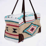 Rectangular weekender bag made of woven material, primarily tan and white with diamond and stripe design in orange, dark red, turquoise and black, with brown suede handles and bottom corners against white background.