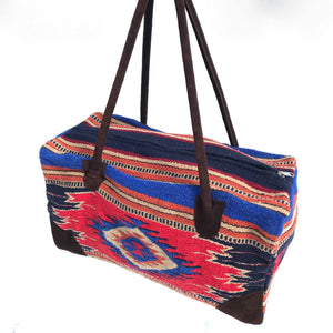 Rectangular weekender bag made of woven material, primarily red with stripe and diamond design in cobalt blue, dark orange, burgundy, tan and black, with brown suede handles and bottom corners against white background.