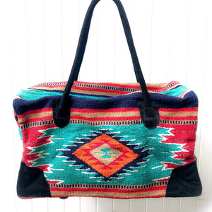 Rectangular weekender bag made of woven material, primarily teal and red with diamond and stripe design in orange, tan, turquoise, navy blue, white and black, with black suede handles and bottom corners against white background.