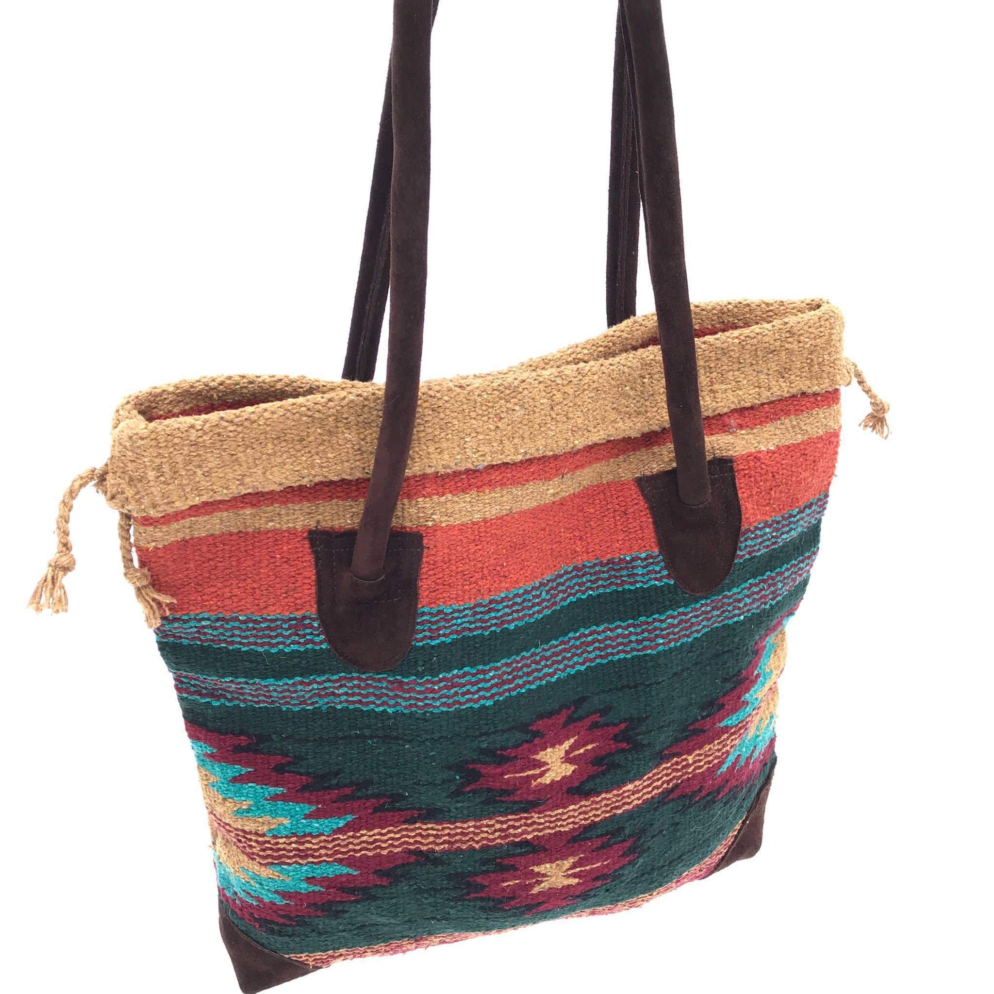 Square tote bag made from woven material, primarily dark green with diamond design in burgundy, turquoise, gold and black, with accent stripes in the same colors, handles and bottom corners in dark brown suede, shown against white background.