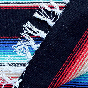 Close up of woven blanket showing wide black stripe alternating with section of narrow stripes in blue, teal, white, black, tan and red, with blanket corner turned over showing white fringed edge.
