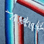 Close up of woven blanket showing wide grey stripe alternating with section of narrow stripes in blue, teal, white, black, tan and red, with blanket corner turned over showing white fringed edge.