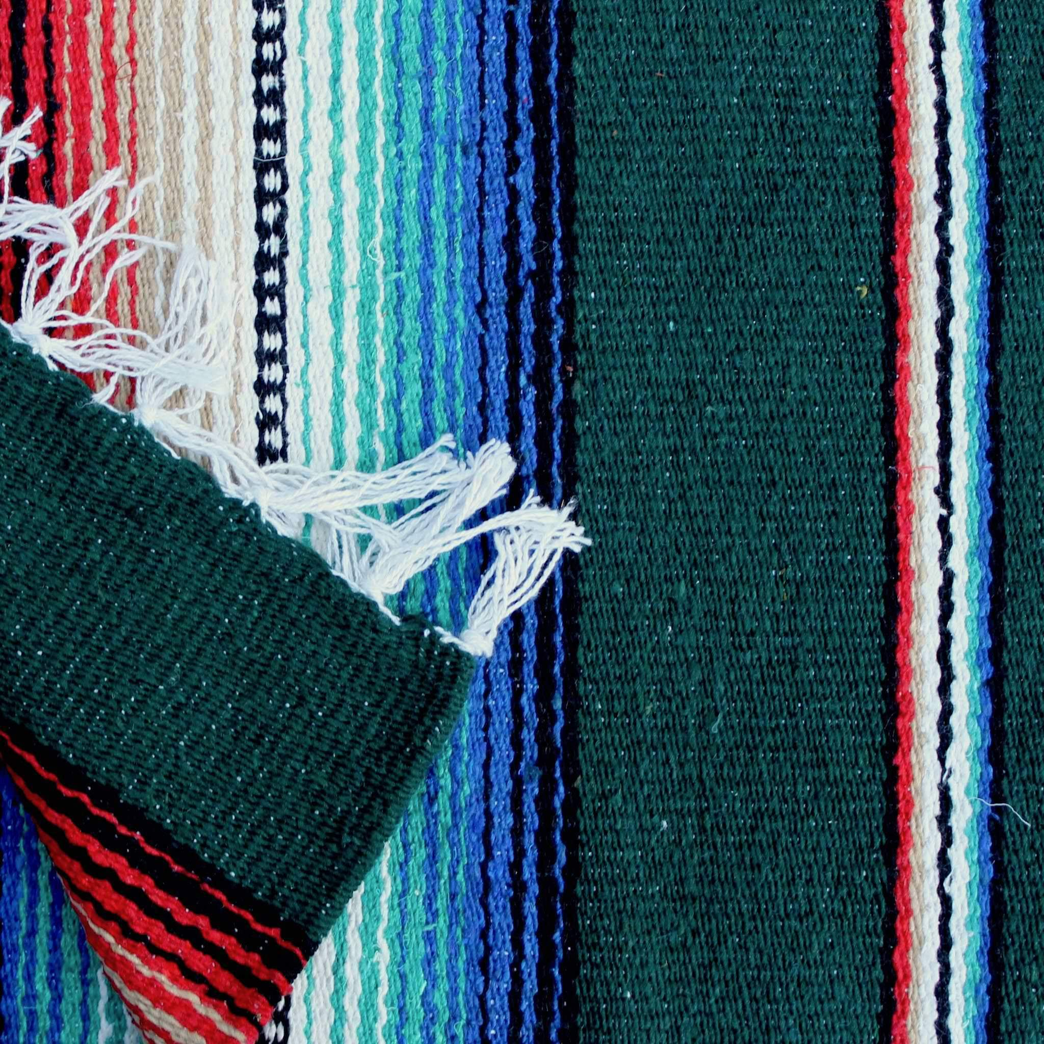 Close up of woven blanket showing wide hunter green stripe alternating with section of narrow stripes in blue, teal, white, black, tan and red, with blanket corner turned over showing white fringed edge.
