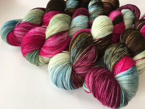 hand dyed sock yarn skeins in brown, pink, blue and green