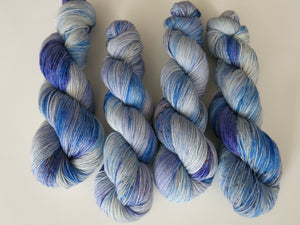 hand dyed superwash merino and nylon sock yarn in blue with speckles