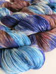 hand dyed blue and brown speckled merino sock yarn skeins
