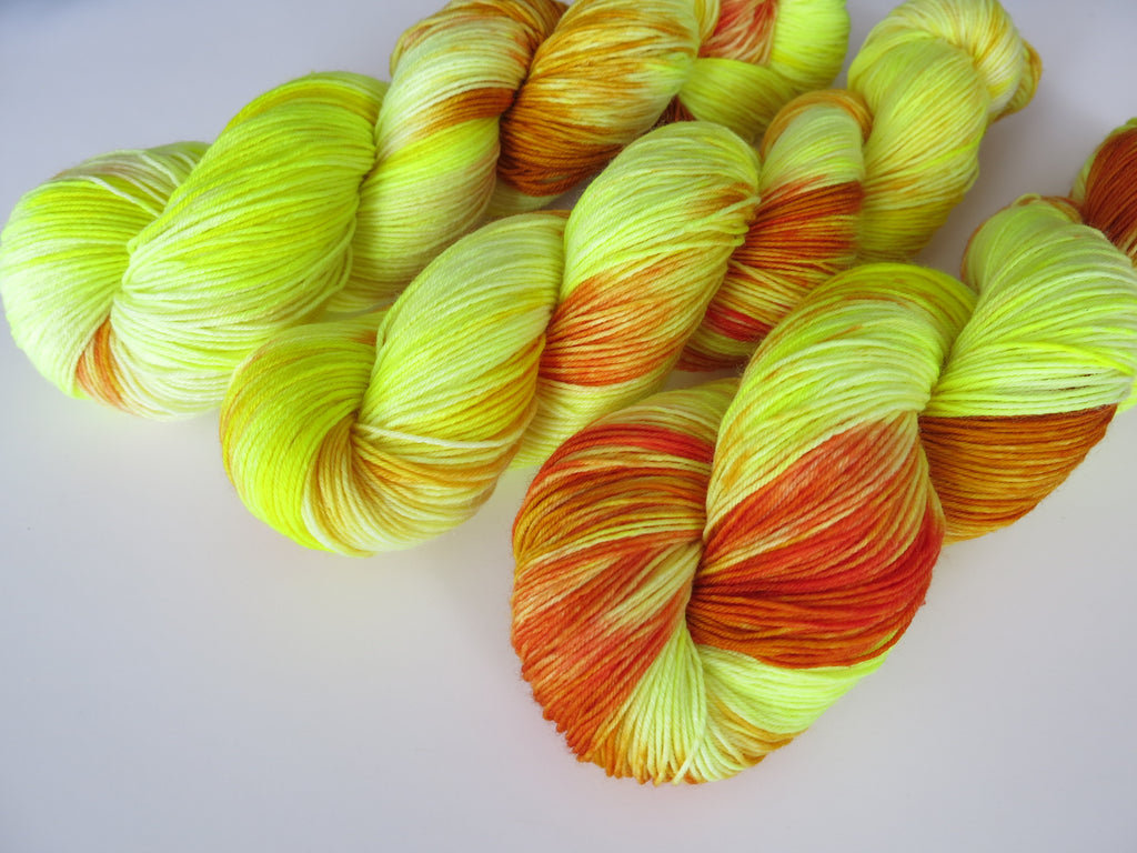 indie dyed yellow uv reactive sock yarn skeins