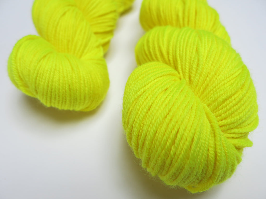 hand dyed uv reactive yellow merino dk yarn skein