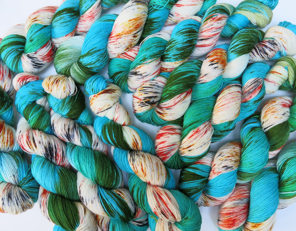 indie dyed speckled orange and green sock yarn skeins