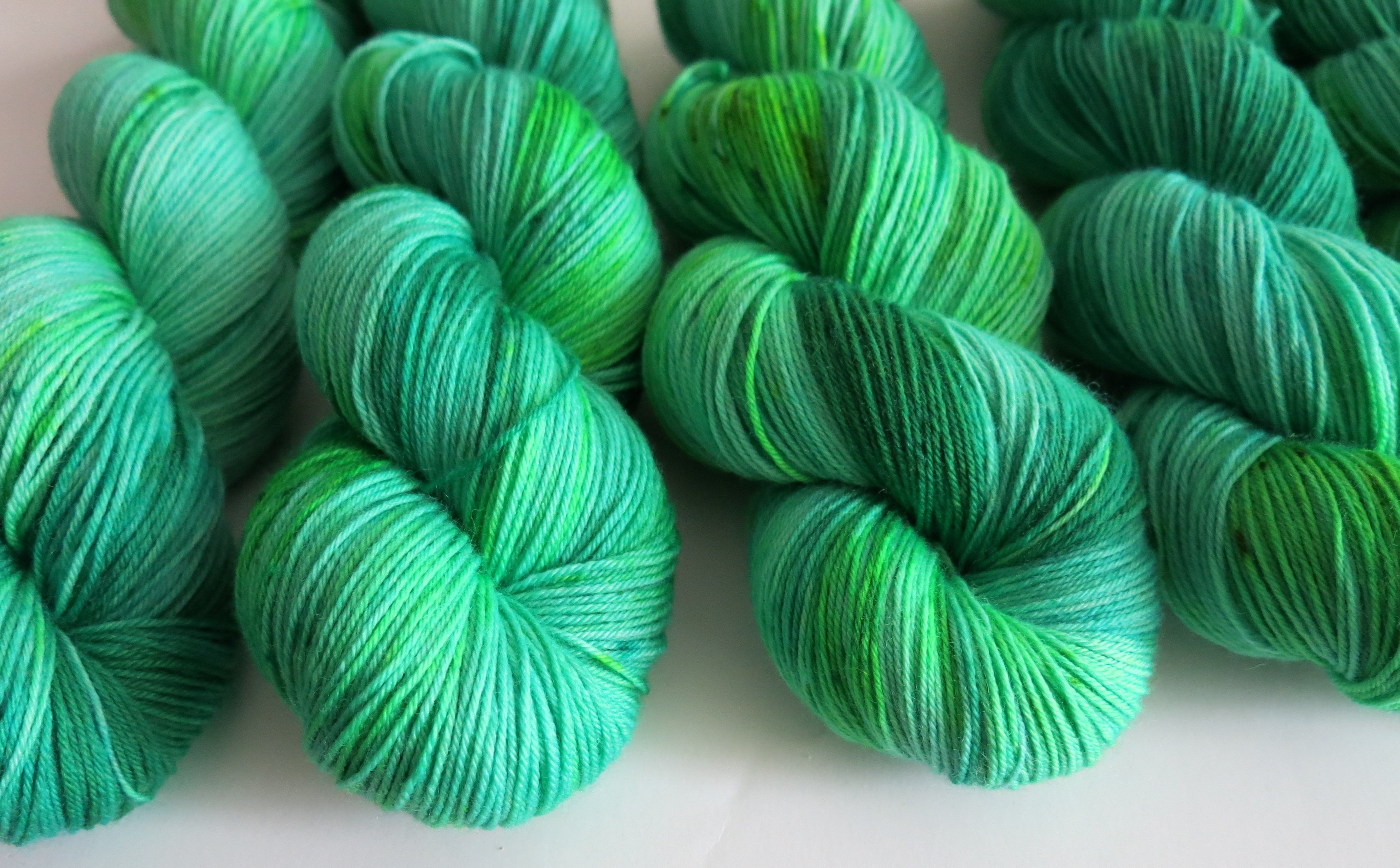 hand dyed uv reactive green merino sock yarn skeins