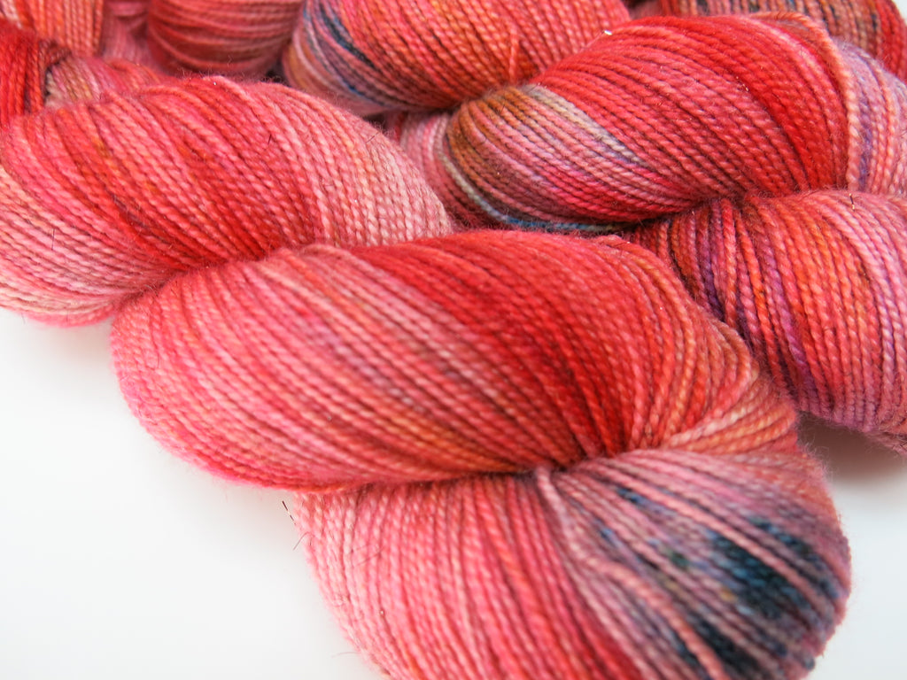 hand dyed 100g skeins of sparkly sock yarn in red with blue speckles