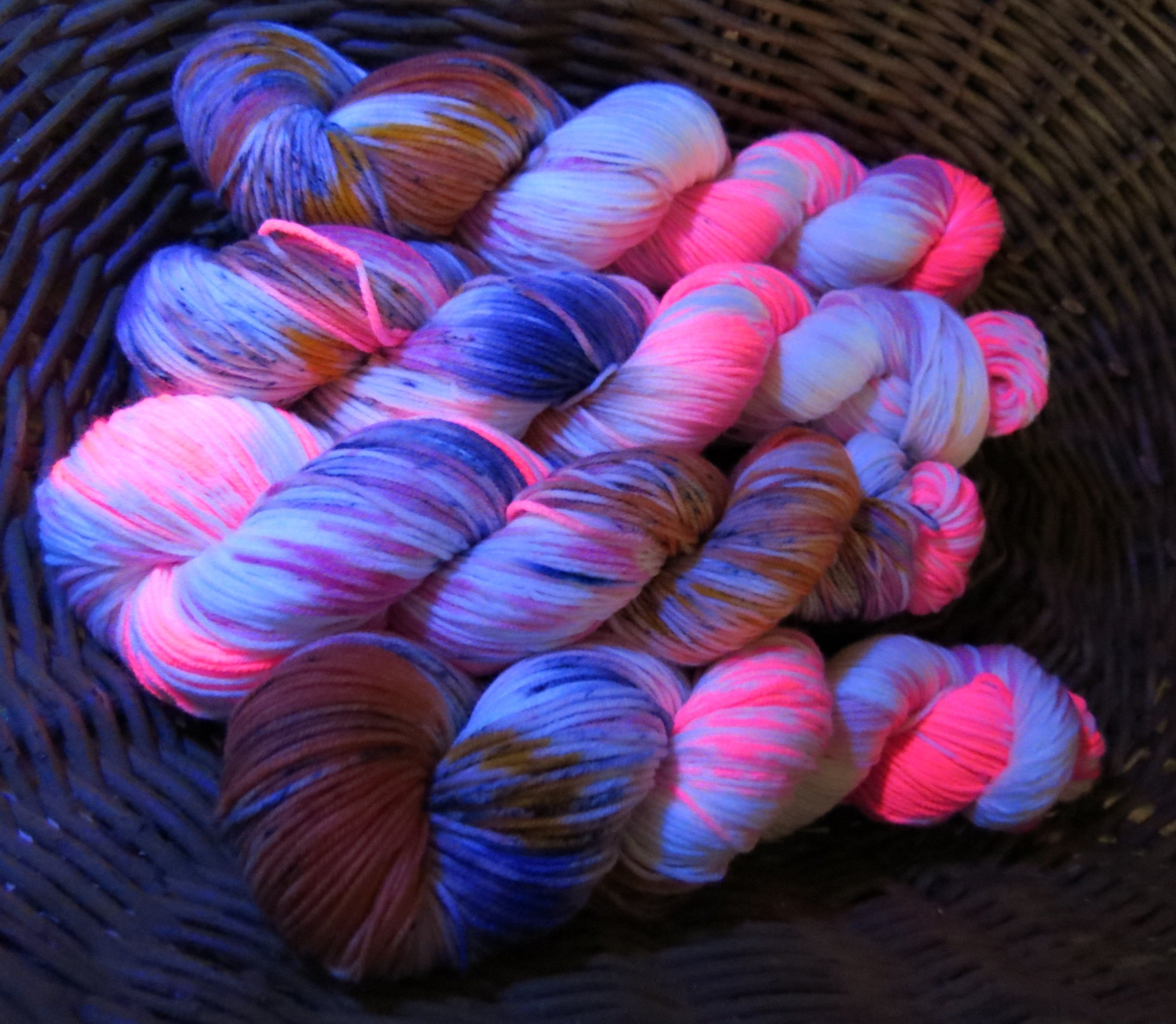 uv reactive pink and orange DK yarn skein under black light