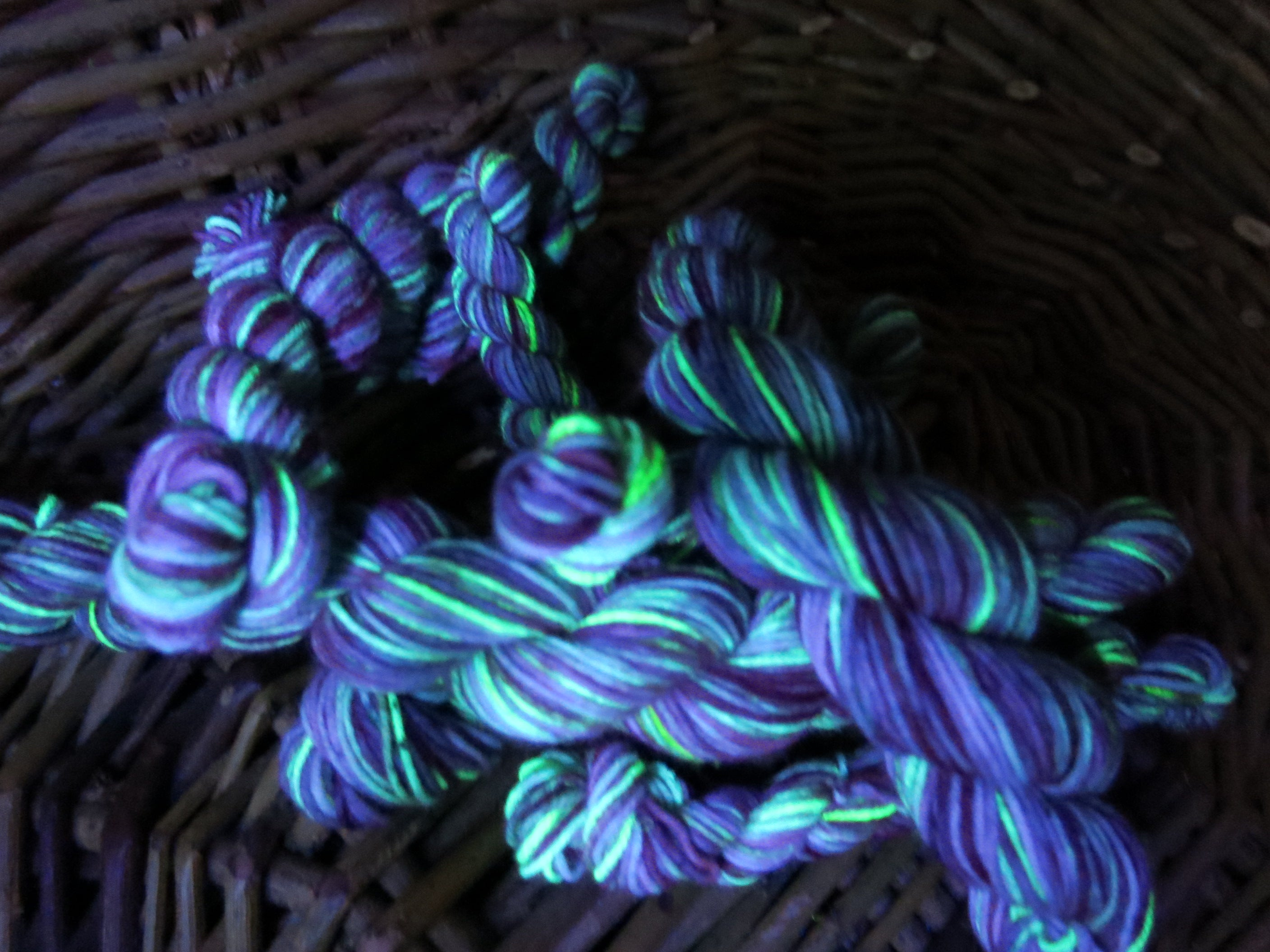 indie dyed blue green uv reactive sock yarn under black light