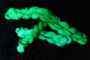 hand dyed uv reactive christmas sock yarn under black light
