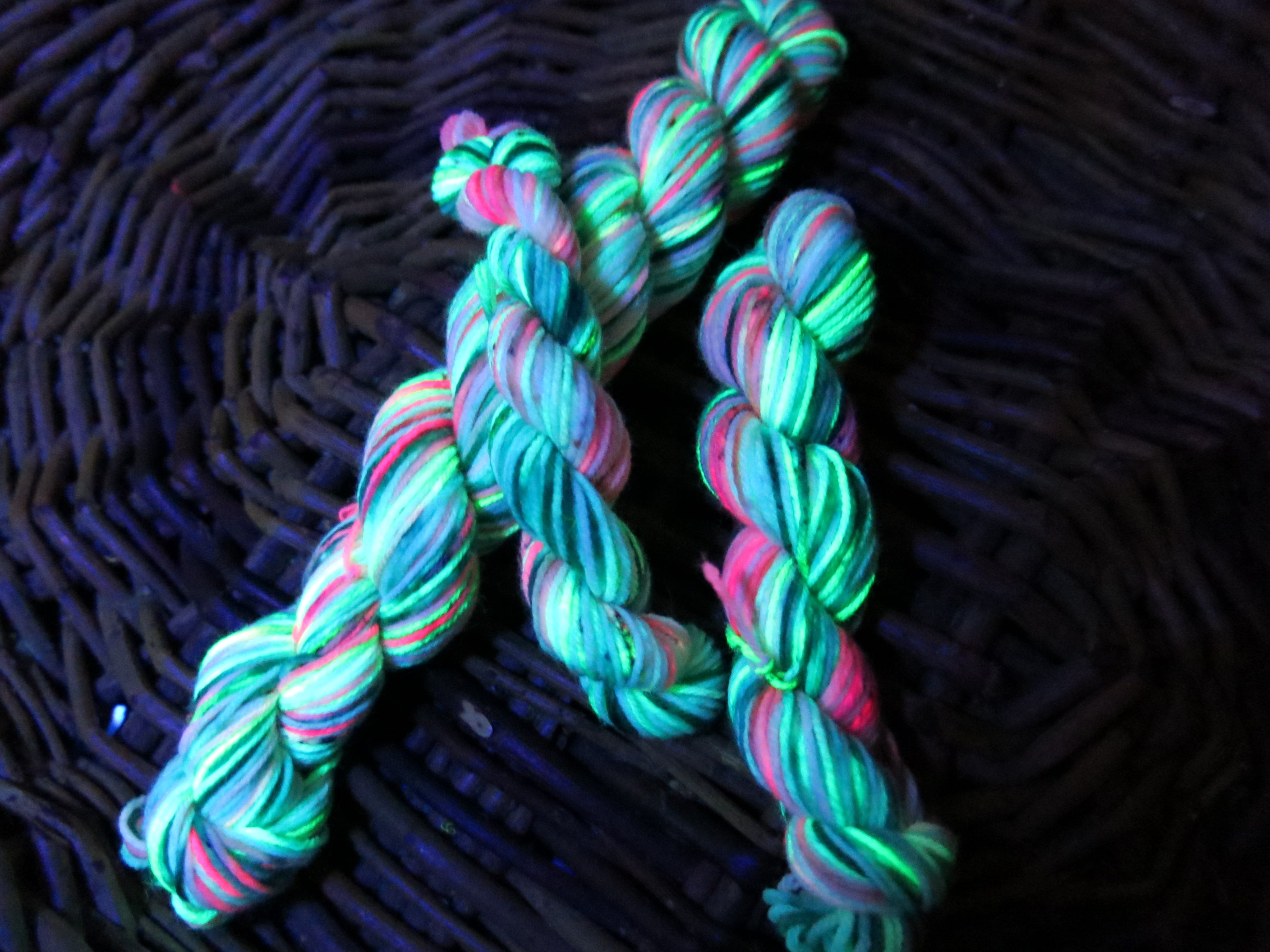 hand dyed uv reactive pink and green sock yarn under black light