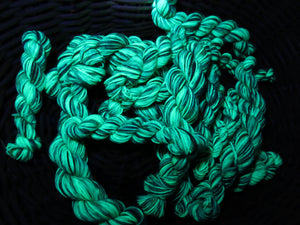 hand dyed green uv reactive yarn glowing under black light
