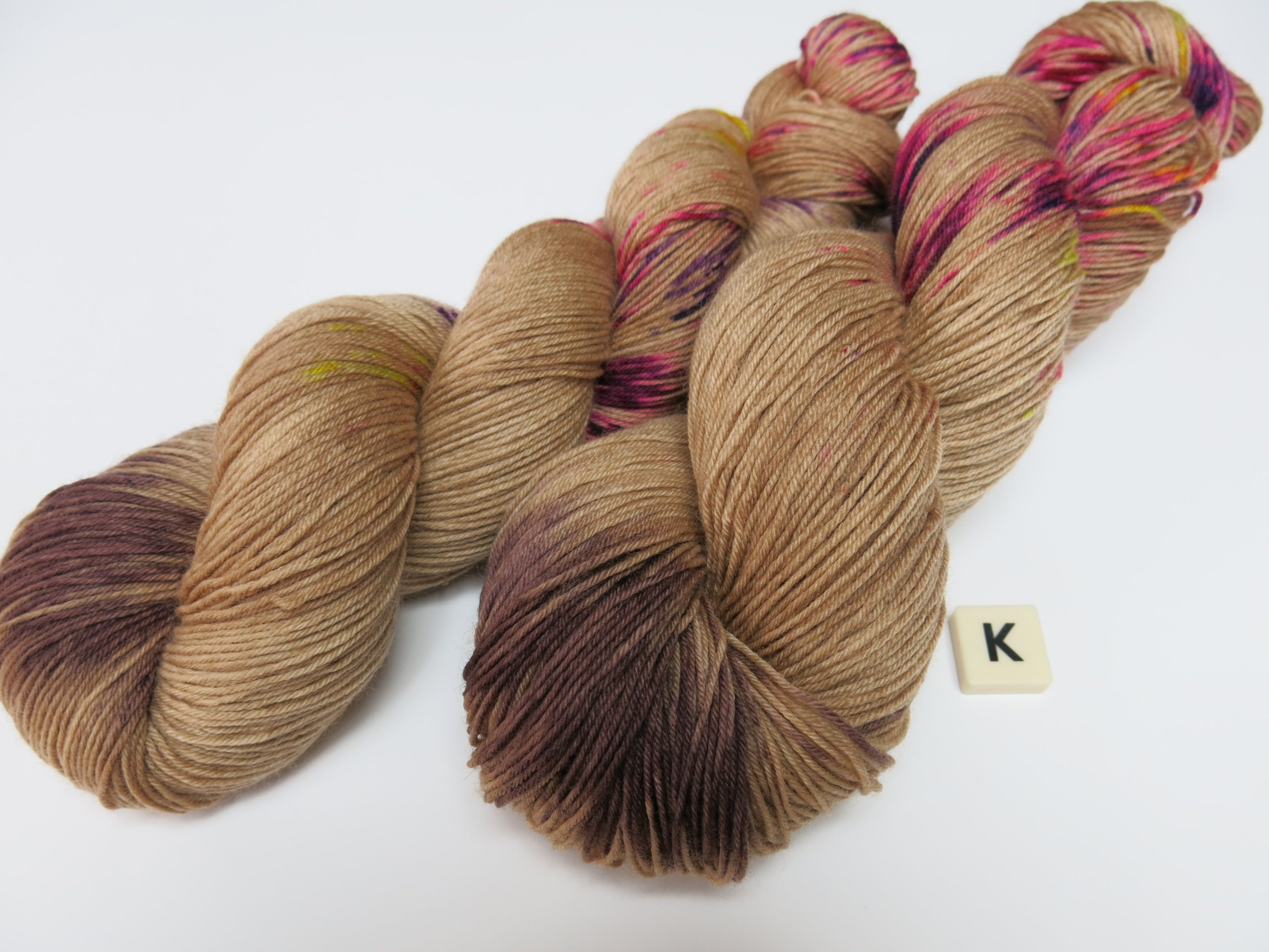 hand dyed brown and neon speckled uv reactive yarn skeins