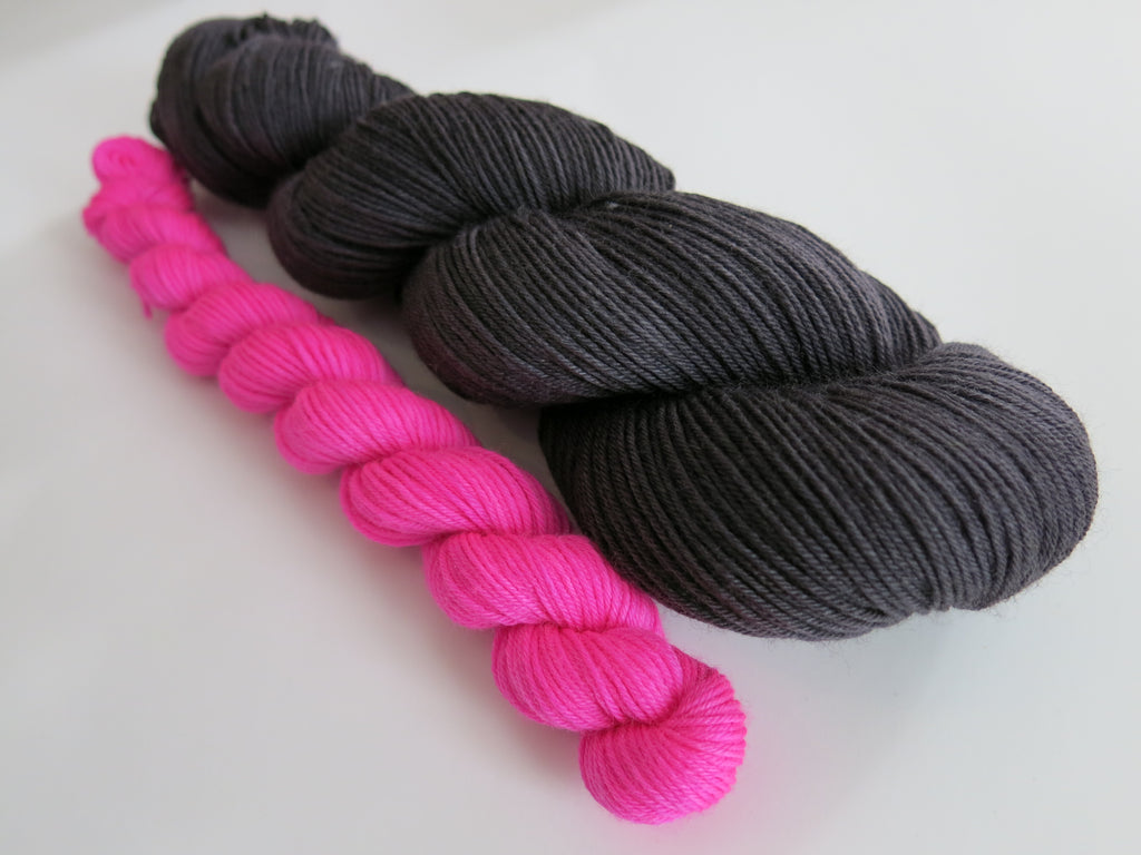 hand dyed black yarn with a neon pink mini skein