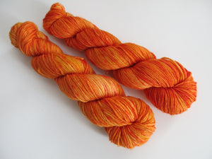indie dyed orange speckled yarn for sock knitting